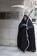 A court closure protester dressed as the Grim Reaper poses in front of the sigh to the Ministry of Justice (MOJ), central London.