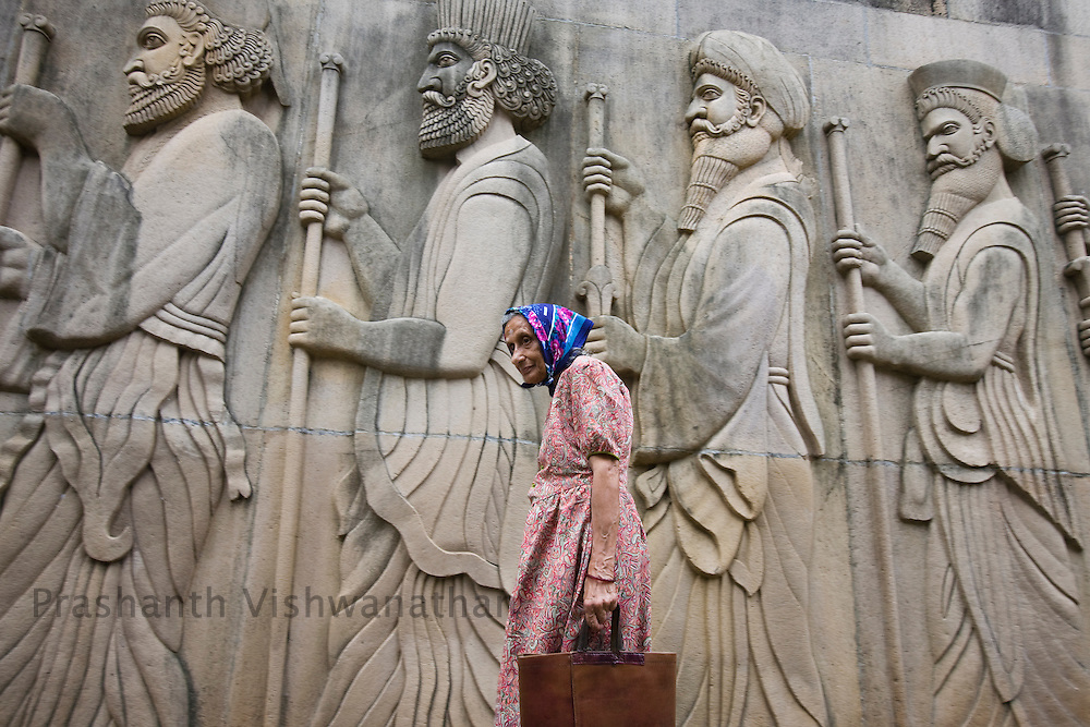 A Parsi woman walks past a bas-relief depicting early Zoroastrians at the  Kappawala Agiary, or Fire Temple, on Navroze, the Parsi new year, in Mumbai, India, Tuesday, Aug. 19, 2008. Parsis, also known as Zoroastrians, worship fire and are followers of the Bronze Age Persian prophet Zarathustra. According to estimates there are only 150,000 Zoroastrians in the world today and more than 80,000 live in India, mostly in Mumbai. Photographer:Prashanth Vishwanathan/Atlas Press