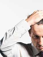 Young Businessman with Hand on Head close-up