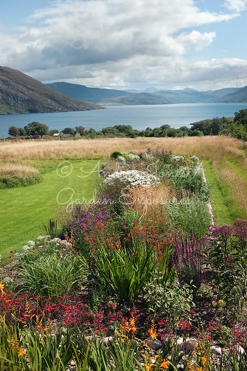 Raised flowering herbaceous border, mown lawns and meadow with view to little Loch Broom<br /> <br /> 2 Durnamuck, Little Loch Broom, Wester Ross, Scotland