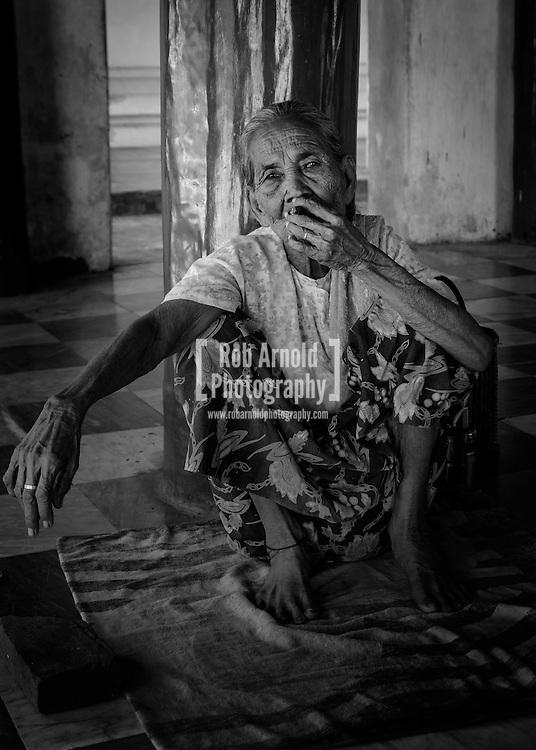 An elderly Myanmar woman smoking a Cheroot (cigar) made from tobacco , corn husk and tha nat phet leaves inside the Shwezigon Pagoda, Nyaung-U.
