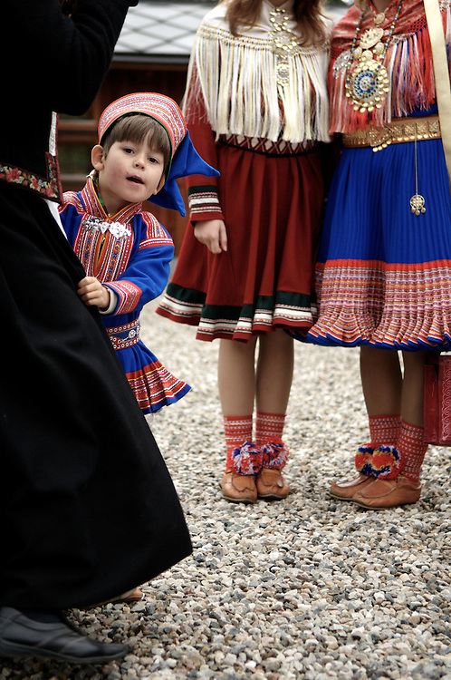 A boy peers from behind his father at a Sami wedding.