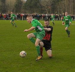 Westport United's Darren Browne gets a tackle on   Usher's Wayne Walker during the FAI Junior Cup 6th Rd game against at United Park, Westport<br />