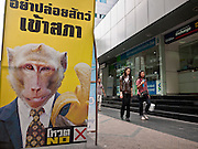 "22 JUNE 2011 - BANGKOK, THAILAND: People walk past a ""vote no"" poster on Silom Rd in Bangkok Wednesday. The ""Yellow Shirts"" are sponsoring a vote no campaign in the upcoming election hoping to negate a win by the Red Shirts and their political party, Pheua Thai. Yingluck Shinawatra, leader of the Pheua Thai party is running against  incumbent Prime Minister Abhisit Vejjajiva, head of the Democrat party. Yingluck is the youngest sister of exiled former Prime Minister Thaksin Shinawatra, deposed by a military coup in 2006. Yingluck is currently leading in opinion polls, running well ahead of the Democrat party, which in one form or another has ruled Thailand for most of the last 60 years.   Photo by Jack Kurtz"