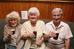 A group of elderly friends enjoying a drink in the pub,