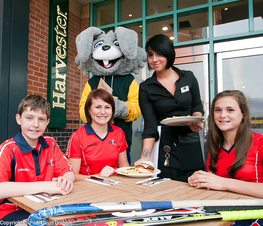 Official opening of Sheffield's new Harvester Salad & Grill at Meadowhall..Harvesters mascot  Harvey The Rabbit watches Laura Goodall serve  orders to  Sheffield Hockey club players (left to right ) Callum Grouege, Ali Crewesmith and Jemima Board. .10 November 2011. Image © Paul David Drabble