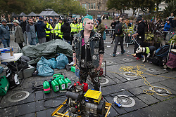 © Licensed to London News Pictures . 03/10/2015 . Manchester , UK . A woman stands over a generator powering the sound system . Protesters against the Conservative government's policies hold a non-stop rave in Piccadilly Gardens in Manchester City Centre ahead of the Conservative Party's annual conference . Photo credit: Joel Goodman/LNP
