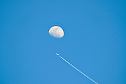 Day time moon on blue sky background A jet plane is seen crossing the moon