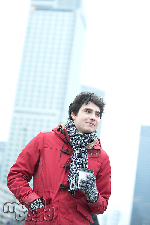 Thoughtful man in warm clothing holding disposable cup outdoors