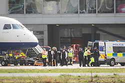 © Licensed to London News Pictures. 10/10/2019. London, UK. Police officers search an Extinction Rebellion protester after he was removed from on top of a British Airways plane at London City Airport. Protesters planned to occupy the terminal building in a 'Hong Kong-style' shutdown as part of ongoing protests calling on government departments to tackle the Climate Emergency. Photo credit: Rob Pinney/LNP