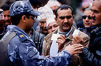 "Kathmandu, 18 February 2005.  Nepali workers displaying their ID cards to a policeman. On the nation's Democratic Day the Armed Police Forces are blocking ordinary people from moving around in the city. Local transports has been banned for most of the day. Authorities have also, once again, cut off local telephone lines. ""Today we have arrested several people. They were planning pro-democracy rallies, but we didn't give them any chance to demonstrate"", a police officer says"
