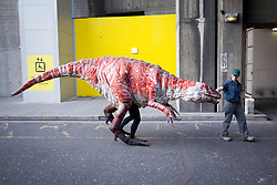 © Licensed to London News Pictures. 18/02/2013. London, UK. An actor in a costume representing an 'Australovenator', a species of dinosaur discovered in Australia in 2009, is led away after meeting children on London's Southbank today (18/02/2013) as part of the 'Dinosaur Petting Zoo'. The 'Dinosaur Petting Zoo', an interactive puppetry show by company Erth, runs from the 18th to the 20th of February as part of London's Southbank Centre's 'Imagine Children's Festival'. Photo credit: Matt Cetti-Roberts/LNP