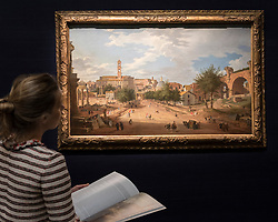 "© Licensed to London News Pictures. 01/07/2016. London, UK.  A staff member views ""Rome, a view of the Forum looking towards the Capitol"" by Giovanni Paolo Panini (est. GBP 1-1.5 million), at the preview of Sotheby's London Old Masters evening sale which takes place 6 July.   Photo credit : Stephen Chung/LNP"
