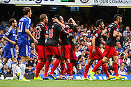 Swansea City players celebrate the opening goal against Chelsea during the Barclays Premier League match at Stamford Bridge, London<br /> Picture by David Horn/Focus Images Ltd +44 7545 970036<br /> 13/09/2014