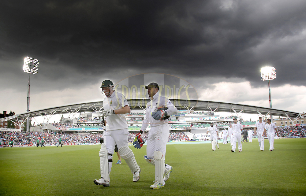 © Andrew Fosker / Seconds Left Images 2012 - Under dark skies and rain falling  the players led by South Africa's Graeme Smith (c) (L) and England's Matt Prior leave the field just after tea - England v South Africa - 1st Investec Test Match -  Day 2 - The Oval  - London - 20/07/2012 - Photoshop dodge & burn