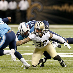Aug 15, 2014; New Orleans, LA, USA; New Orleans Saints strong safety Kenny Vaccaro (32) trips up Tennessee Titans wide receiver Kendall Wright (13) during first quarter of a preseason game at Mercedes-Benz Superdome. Mandatory Credit: Derick E. Hingle-USA TODAY Sports