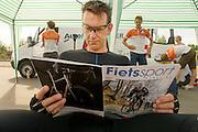 Wil Baselmans leest het blad Fietssport. In Schipkau bereidt het Human Power Team Delft en Amsterdam zich met fietser Wil Baselmans voor op het laagland sprintrecord met de VeloX3. In september wil het team, dat bestaat uit studenten van de TU Delft en de VU Amsterdam, een poging doen het wereldrecord snelfietsen te verbreken, dat nu op 133 km/h staat tijdens de World Human Powered Speed Challenge.<br /> <br /> Wil Baselmans reads the magazine Fietssport (cycling sport). At the Dekra test track in Lausitz the Human Power Team Delft and Amsterdam is preparing the VeloX3 with rider Wil Baselmans for the attempt to set a new lowland sprint record on a bicycle. With the special recumbent bike the team, consisting of students of the TU Delft and the VU Amsterdam, also wants to set a new world record cycling in September at the World Human Powered Speed Challenge. The current speed record is 133 km/h.