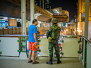 19 JANUARY 2014 - BANGKOK, THAILAND: A Thai civilian talks to a soldier on duty in the Phrom Phong BTS Station after a candlelight vigil for peace in a nearby park Sunday night. As violence at anti-government protest sites has increased, Thai soldiers have become a more common presence in Bangkok, especially around high value areas like the BTS system and train stations. Hundreds of people came to Benjasiri Park, a few hundred meters from the anti-government protest site in Asok Intersection, Sunday evening to pray for peace and rally for a respect for democracy Sunday. The vigil took place a few hours after a two explosive devices, thought to be grenades, were thrown at the protest site near Victory Monument, several kilometers north of Asok. The grenade attack Sunday was the 2nd daytime grenade attack in three days on anti-government protestors. No arrests have been made in the incidents.    PHOTO BY JACK KURTZ
