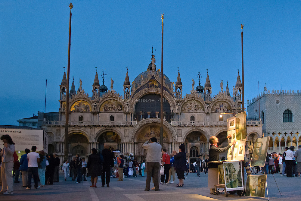 An artist hangs his paintings for the evening crowd at San Marco (St. Mark's) Square.