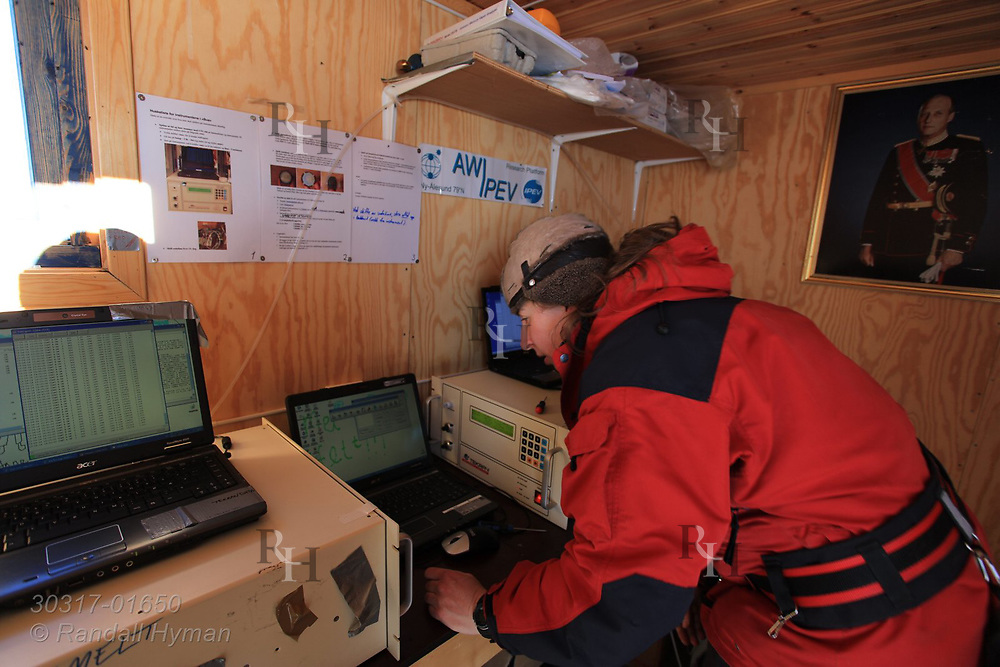 Woman checks equipment in research shed at the international science village of Ny-Alesund on Spitsbergen island in Kongsfjorden; Svalbard, Norway.