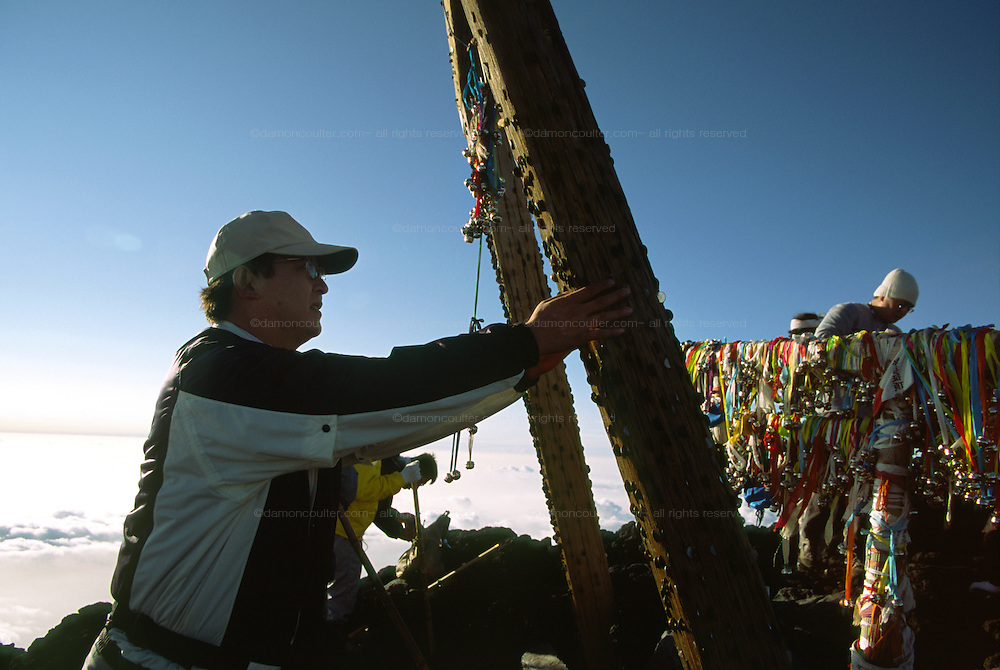 A climber knocks a coin into the woodwork of a small torii gate for luck on the sumit of Mount Fuji, at 3,776 metres, the highest peak in Japan. Yamanashi Prefecture, Japan August 2005