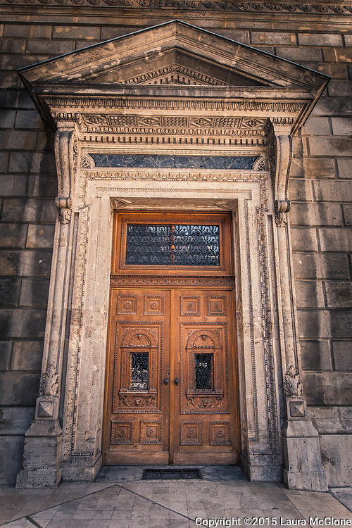 Brown wooden carved door with stone surround, Budapest Hungary