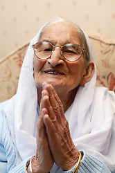Portrait of a Sikh elderly grandmother with hands together in a greeting gesture,