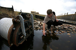 CANADA ALBERTA FORT MCMURRAY 19JUL09 - Greenpeace campaigner Christoph von Lieven takes a water sample from a waste pipe leading to a Syncrude tailings pond north of Fort McMurray, northern Alberta, Canada...jre/Photo by Jiri Rezac / GREENPEACE..© Jiri Rezac 2009