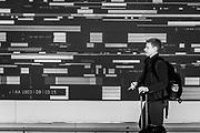Digital Art video wall by artist Refik Anadol is the background as a passenger walks by at Charlotte Douglas International Airport