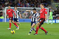 WBA's Shane Long © holds off Cardiff city's Ben Turner. Barclays Premier league, Cardiff city v West Bromwich Albion at the Cardiff city Stadium in Cardiff, South Wales on Saturday 14th Dec 2013. pic by Andrew Orchard, Andrew Orchard sports photography.