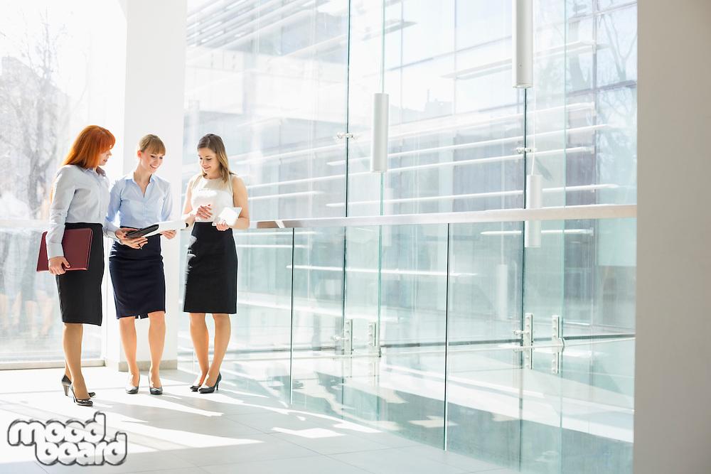 Full-length of businesswomen doing paperwork in office