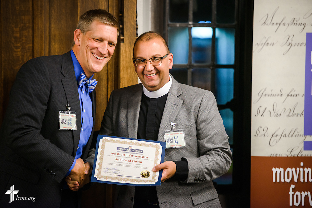"LCMS Foundation President David Fiedler presents an award to the Rev. Bart Day, executive director of LCMS Office of National Mission, on behalf of the Rev. Ross Johnson, director of LCMS Disaster Response, for his compilation of essays in ""Mercy in Action: Essays on Mercy, Human Care, and Disaster Response,"" during the ""Trumpeting the Treasures"" Concordia Historical Institute 42nd annual awards banquet on Thursday, Nov. 10, 2016, at Concordia Seminary, St. Louis. LCMS Communications/Erik M. Lunsford"