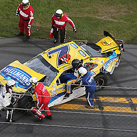 Regan Smith (7) climbs from his crashed car after it flipped on the front stretch during the Alert Today Florida 300 XFinity Series race at Daytona International Speedway on Saturday, February 21, 2015 in Daytona Beach, Florida.  (AP Photo/Alex Menendez)