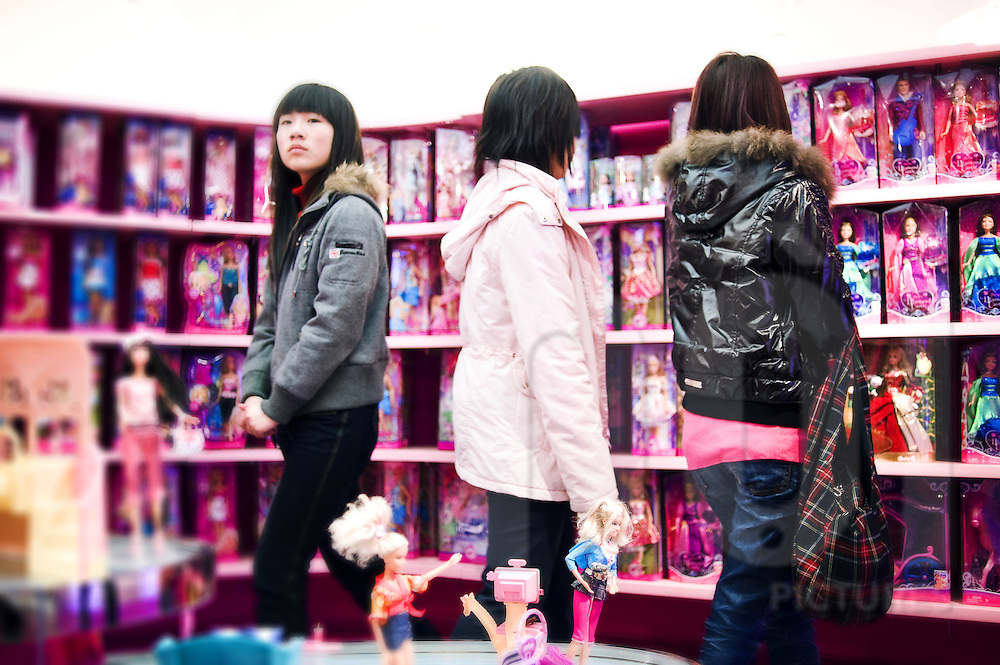 Some chinese girls visit Barbie's store and overlook at the various dolls aligned on shelves. Shanghai, China, Asia.