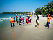 """13 FEBRUARY 2019 - SIHANOUKVILLE, CAMBODIA: Cambodians walk along Ocherteal Beach in Sihanoukville. Chinese casinos being built are in the skyline behind them. There are about 80 Chinese casinos and resort hotels open in Sihanoukville and dozens more under construction. The casinos are changing the city, once a sleepy port on Southeast Asia's """"backpacker trail"""" into a booming city. The change is coming with a cost though. Many Cambodian residents of Sihanoukville  have lost their homes to make way for the casinos and the jobs are going to Chinese workers, brought in to build casinos and work in the casinos.      PHOTO BY JACK KURTZ"""