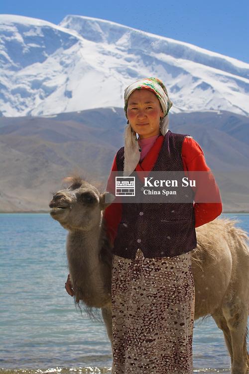 Kirghiz girl with baby camel by Karakuli Lake, Mt. Kunlun behind, Pamir Plateau, Xinjiang, Silk Road, China