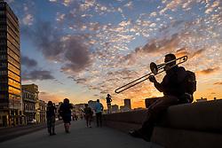 Trombone player on Havana's seaside malecon at sunset