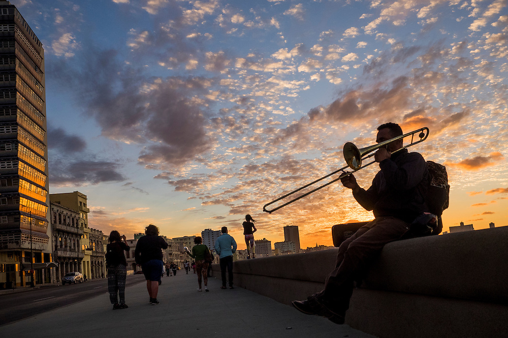 Trombone player on Havana's seaside malecon at sunset