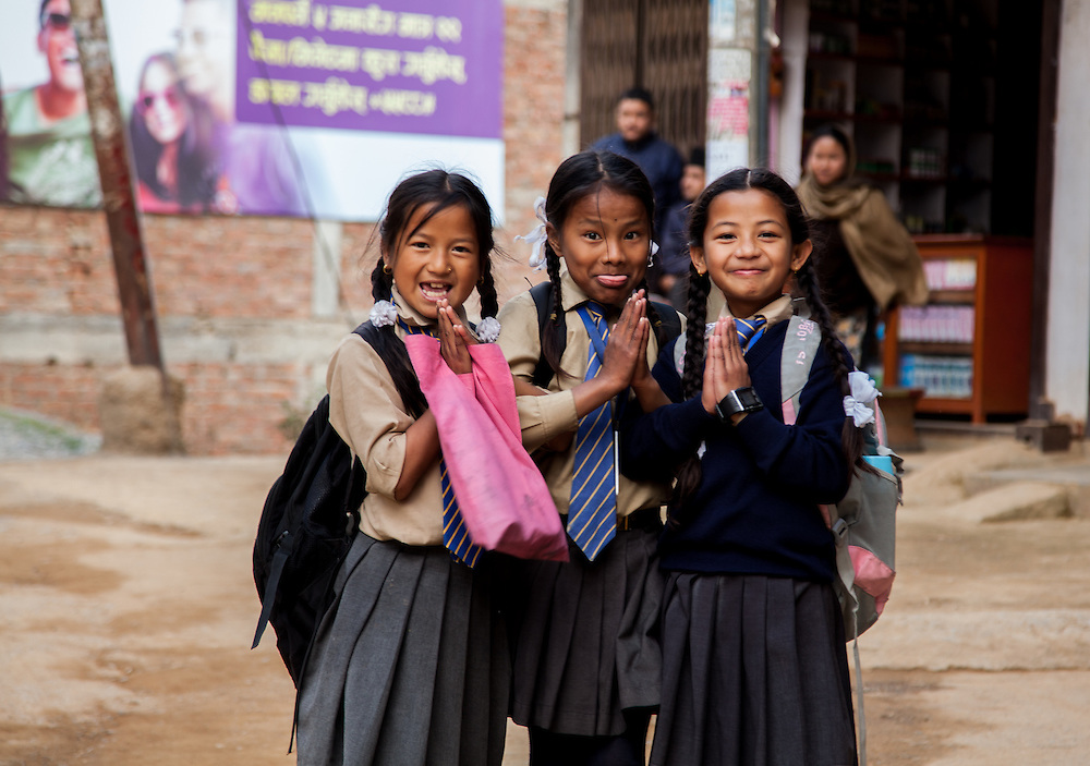 Three young school girls react to being photographed