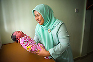 Midwife Een Sumarni with a one-day old babygirly in Islam Jakarta Pondok Kopi Hospital in Jakarta Indonesia.