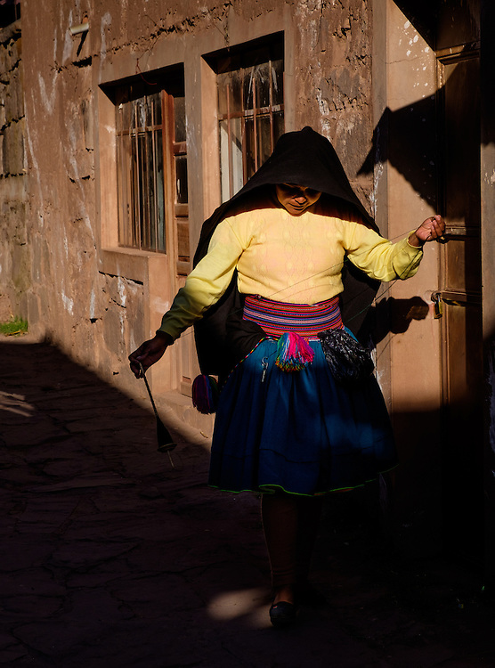 TAQUILE ISLAND, PERU - CIRCA OCTOBER 2015: Woman webing wool and walking in the strets of Taquile Island, in Lake Titicaca, Peru.