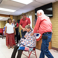Sandy Winright, sitting, is presented her quilt from John Matajcich, and Mayor Jackie Mckinney at the Veterans Helping Veterans building in Gallup Friday.