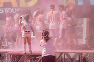 Scranton, Pa. - A woman takes a photograph of a girls on the stage as colorful powder fills the air after the Color Me Rad 5K color run on May 24, 2015.