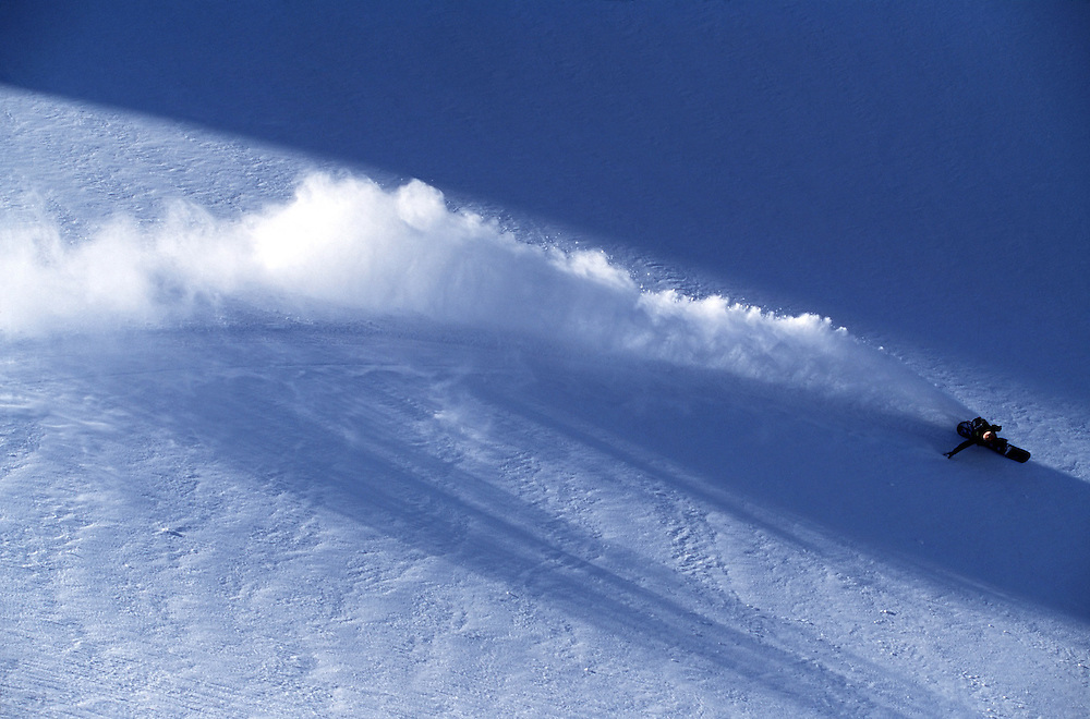 Snowboarder turning in fresh powder snow, Cerro Castor, Tierra del Fuego, Argentina