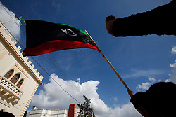 Protestors hold a Kingdom of Libya flag during a protest outside the Libyan Embassy in Attard, outside Valletta, February 22, 2011. The protest was organised by the Libyan community living in Malta against the Libyan government's crackdown on demonstrators in Libya..Photo by Darrin Zammit Lupi