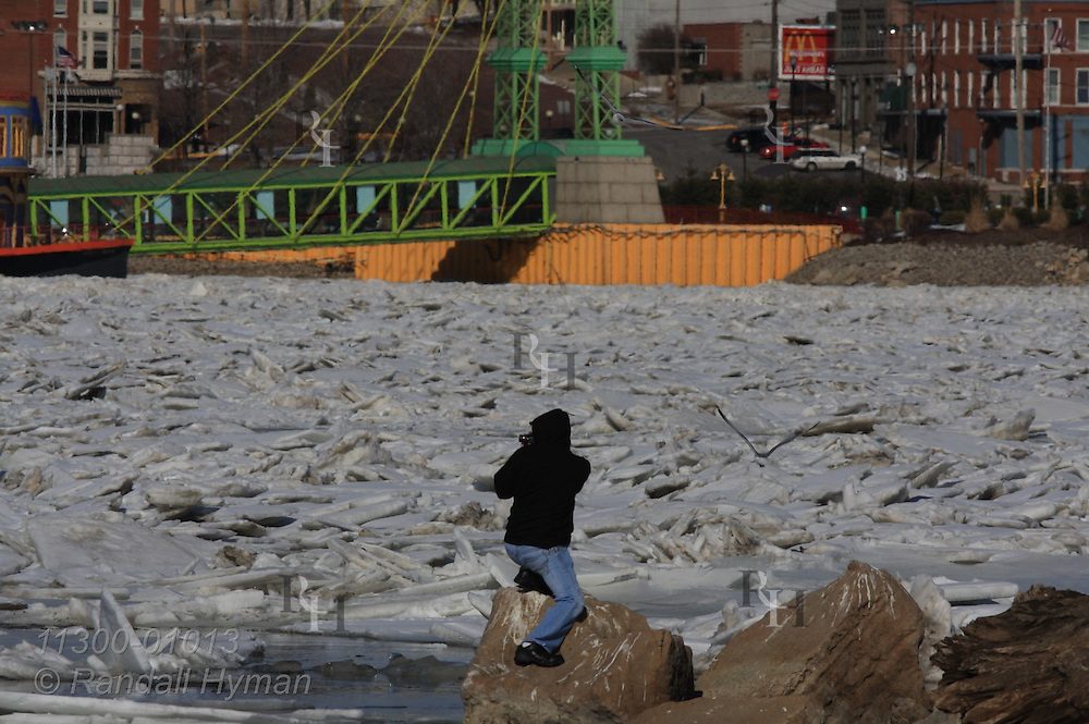Young men explore February ice clogging banks of the Mississippi River across from Alton, Illinois.