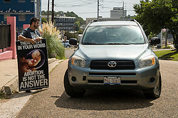 Pro-life activist Keith Dalton, 28, speaks with a patient arriving at the Jackson Women's Health Organization clinic, on Tuesday August 19, 2014, in Jackson, Mississippi. This is the only clinic in the entire state that performs abortions. (Photo © Jock Fistick)