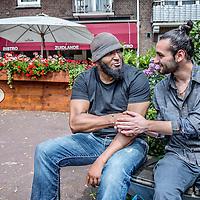 Nederland, Amsterdam, 23 juli 2016.<br />We volgen de Syrische jongen Ibrahim Najjar in de Spaarndammerbuurt in zijn zoektocht naar de ingredienten voor het Syrische kipgerecht Mskhan, een Syrisch ovengerecht met kip, citroen en ui.<br />Hij heeft zijn buren uitgenodigd bij hem te komen eten.<br />Op de foto: Ibrahim begroet en praat met een buurtbewoner.<br /><br /><br /><br /><br />Foto: Jean-Pierre Jans