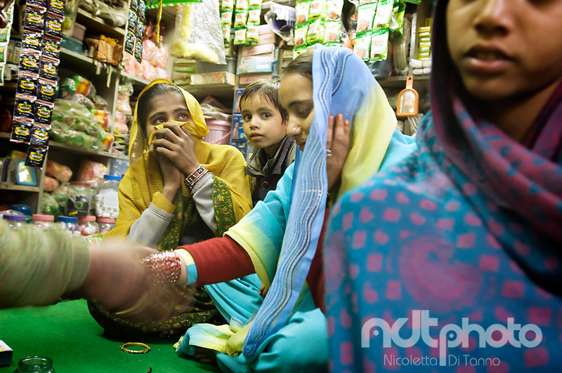 A woman in a shop tries different types of bangles before choosing, together with her relatives. Rajasthan, India