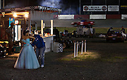 Dressed as a princess Jennifer Knoepfel is helped with her dress while preparing to give out the winner's trophies during the Saturday night stock car races at Agassiz Speedway in Agassiz, BC (2012)